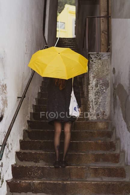 Back view slim lady in coat holding yellow umbrella and standing on stairs between walls in Porto, Portugal — Stock Photo