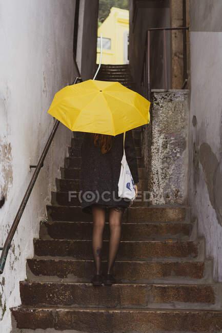 Schlanke Dame im Mantel mit gelbem Regenschirm steht auf einer Treppe zwischen Mauern in Porto, Portugal — Stockfoto