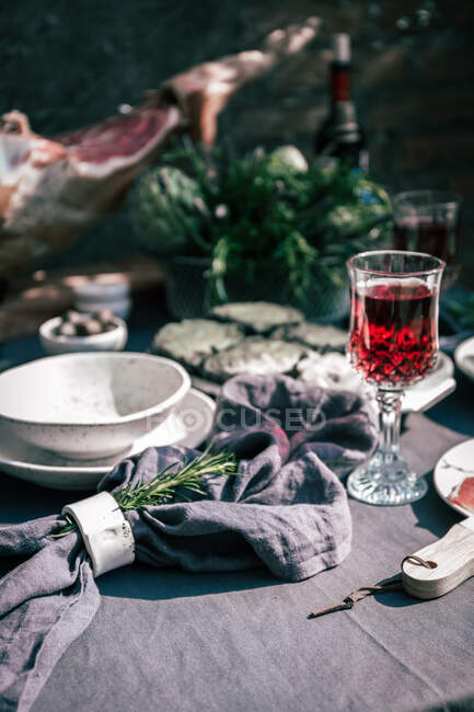 Tablecloth setting with artichokes, red wine and jam serrano leg. — Stock Photo