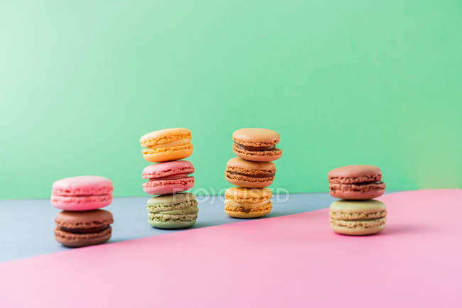 Piles of bright fresh tasty macaroons on pink board on green background — Stock Photo