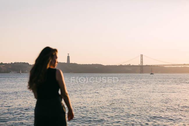 Jovencita vestida de negro parada en el terraplén cerca de la superficie del agua al atardecer y soñando - foto de stock