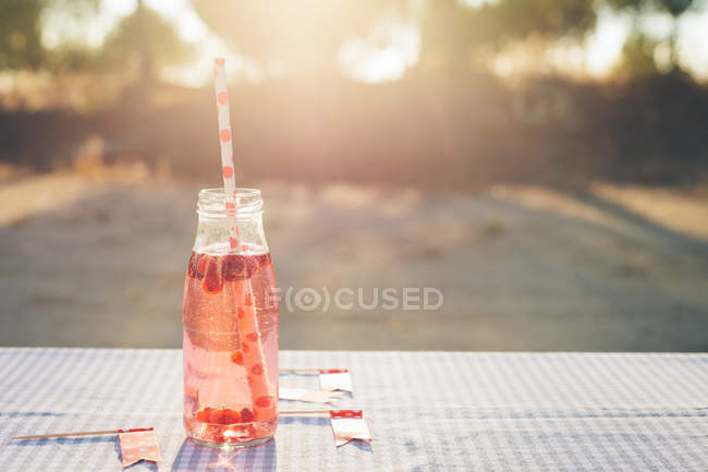 Bottle with fresh fruit drink and drinking straw on table outdoors — Stock Photo