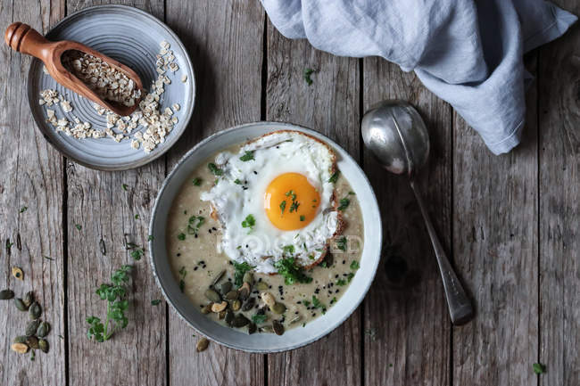 Bowl of yummy grain porridge with fried egg on wooden tablet — Stock Photo