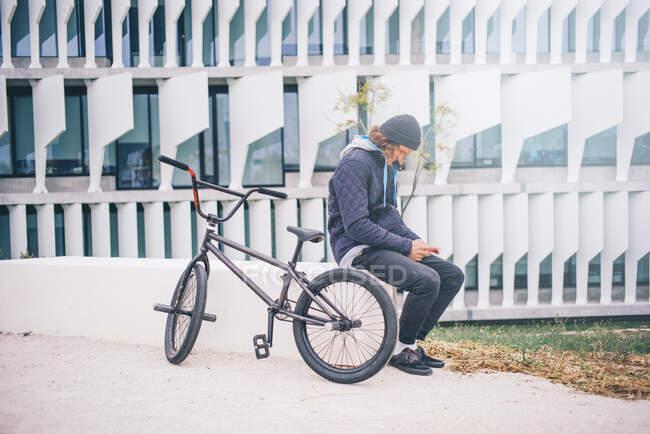 Молодой человек позирует на мобильном и BMX велосипеде. — стоковое фото