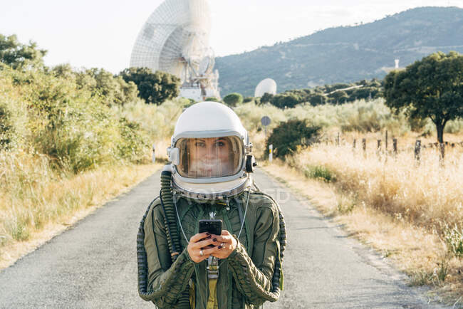 Beautiful female astronaut with mobile phone. — Stock Photo