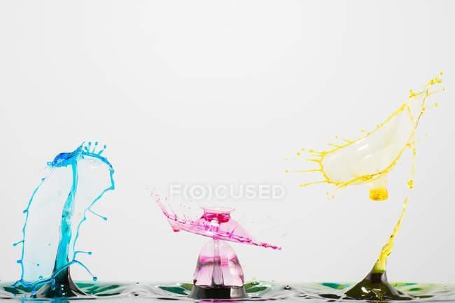 Closeup shot of splash of colorful transparent liquid on white background — Stock Photo