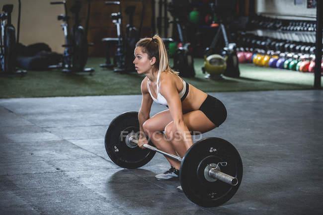 Vue latérale femme en vêtements de sport accroupi avec des haltères avec des plaques de poids dans la salle de gym — Photo de stock