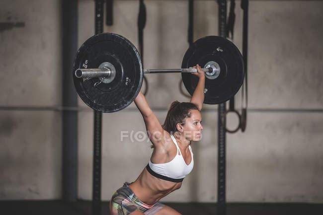 Жінка тримає дзвони з важкими тарілками в спортивному залі. — стокове фото