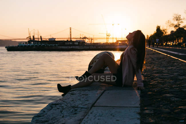 Sensual young woman sitting on embankment near water surface with ship at sunset — стокове фото