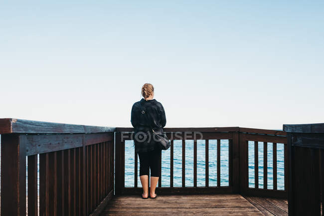 Back view of young female in casual outfit standing near railing on embankment and admiring view of wonderful sea in Altea, Spain — Stock Photo