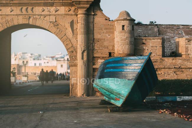 Bateau de pêche ancré près du vieux mur de château en ruine à Marrakech, Maroc — Photo de stock