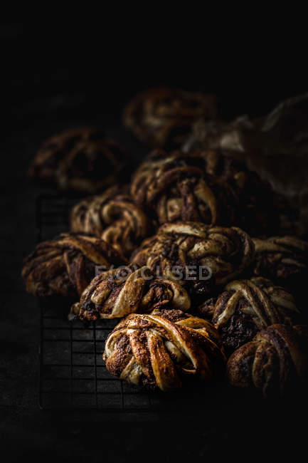 Heap of delicious chocolate buns on metal grating on dark background — Stock Photo