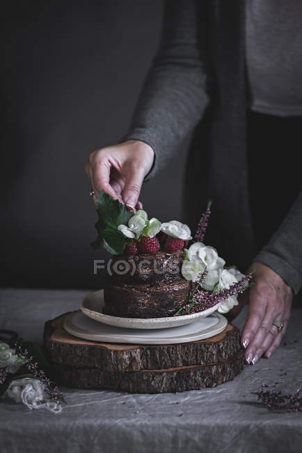 Female hands decorating chocolate cake decorated with raspberries and flowers on plate on wooden stand — Stock Photo