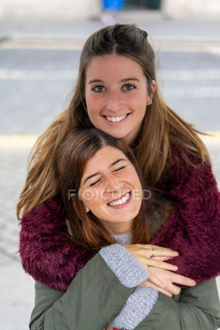 Lady hugging from back cheerful young attractive woman — Stock Photo