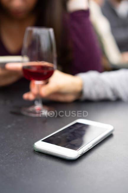 Femme utilisant un smartphone près d'un verre de vin — Photo de stock