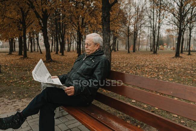 Älterer Mann liest Zeitung im Park — Stockfoto