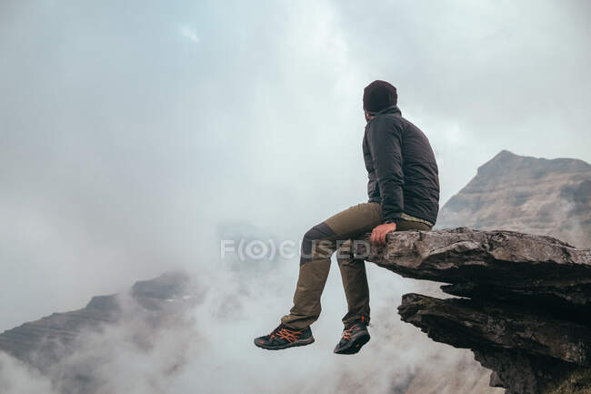 Side view male sitting on stone and looking at Castro Valnera mountain between clouds in Burgos, Spain — Stock Photo