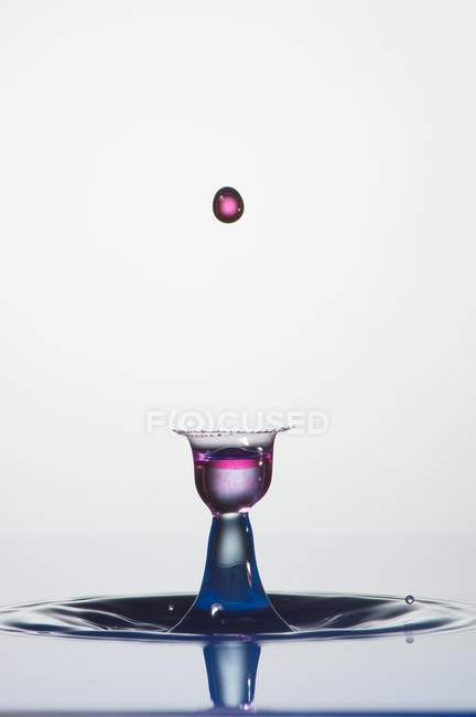 Closeup of splash of transparent liquid of color on gray background — Stock Photo