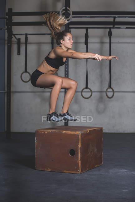 Жінка стрибає на крок у спортивний зал. — стокове фото