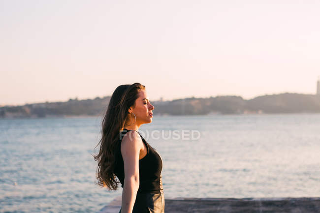 Relaxed charming young woman in black wear standing near water surface in sunny day — Stock Photo