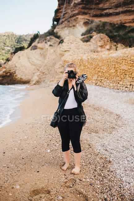 Giovane donna a piedi nudi con macchina fotografica mentre in piedi sulla riva del mare ad Altea, Spagna — Foto stock
