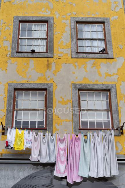 Vecchia facciata gialla di casa con finestre con grate e vestiti appesi al twist in Porto, Portogallo — Foto stock