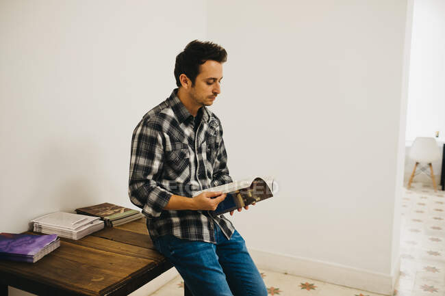Giovane uomo che tiene la rivista vicino al tavolo in camera — Foto stock