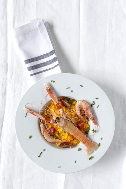 Домашнее паэлья с раковыми шейками и креветки на плите на белой скатерти — стоковое фото