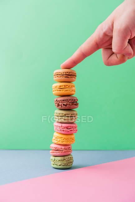 Person de la mano con el dedo en la pila de macarones frescos sabrosos en el tablero azul en fondo verde. - foto de stock