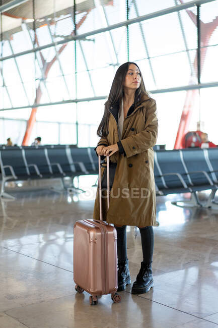 Young woman with suitcase near seats — Stock Photo