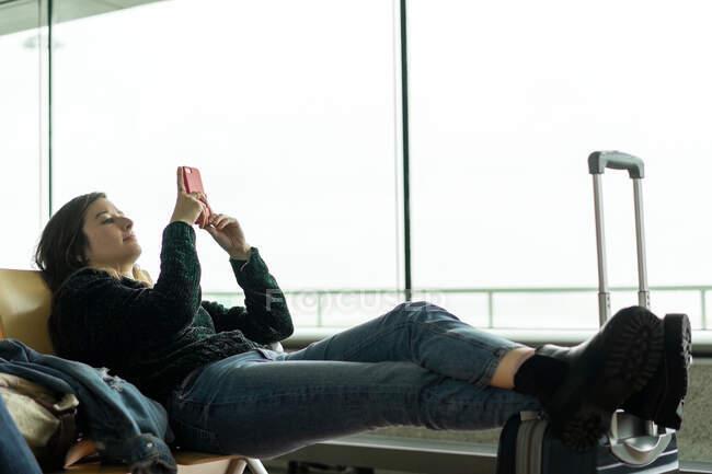Привлекательная дама, пользующаяся мобильным телефоном и сидящая на скамейке с ногами на багажной сумке в зале ожидания аэропорта Порту, Португалия — стоковое фото