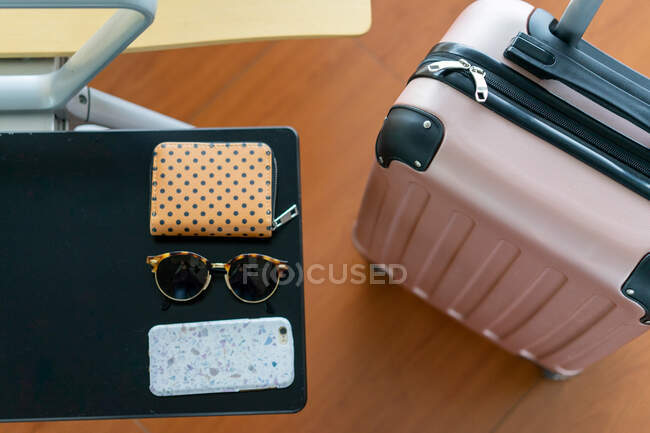 From above rose plastic luggage bag with handle near seat with table with sunglasses, purse and mobile phone in Porto, Portugal — Stock Photo