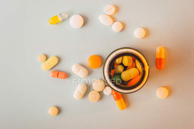 Multicolored pills and capsules scattered and pillbox on white background — Stock Photo
