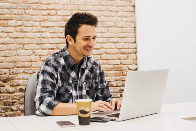 Giovane uomo che utilizza il computer portatile a tavola con tazza e smartphone — Foto stock