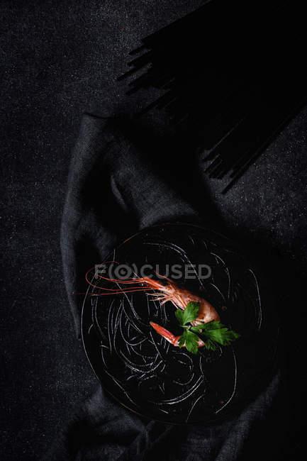 Pasta nera con gamberi servita su piatto nero — Foto stock