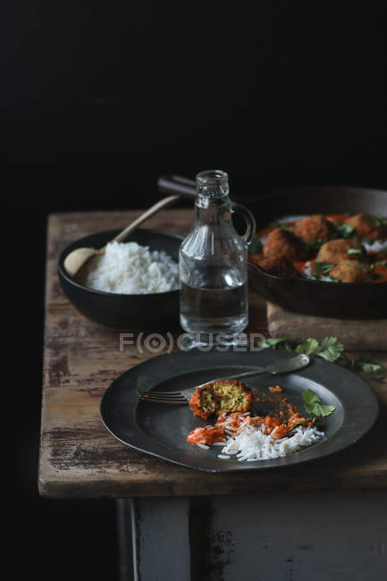Boiled rice and cauliflower and quinoa balls in sauce on wooden table — Stock Photo