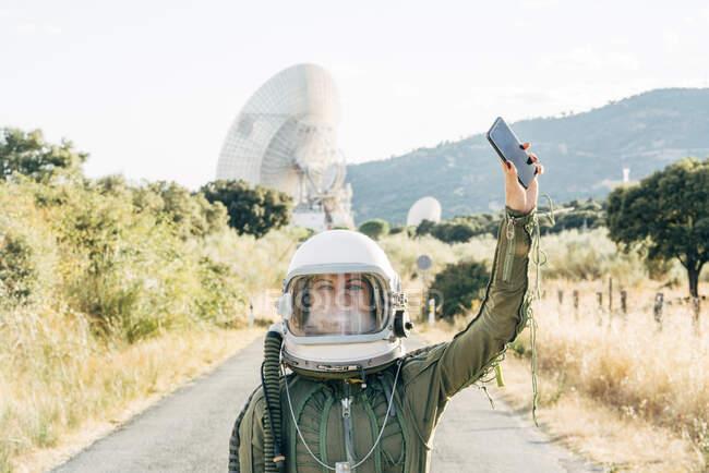 Hermosa astronauta femenina con teléfono móvil. - foto de stock