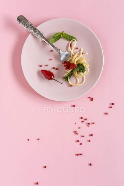 Spaghettis à la sauce tomate et pesto sur plaque sur fond rose — Photo de stock