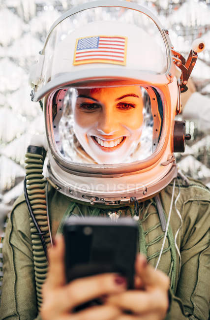 Female astronaut in illuminated vintage helmet with mobile phone — Stock Photo
