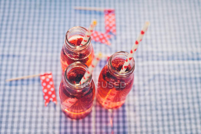 Bottles with fresh fruit drink and drinking straws on checkered tablecloth — Stock Photo