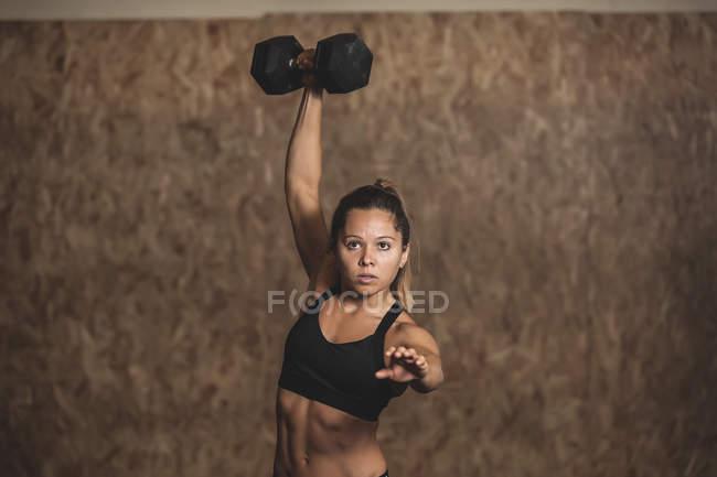 Жінка тренується з тупиками в спортивному залі. — стокове фото
