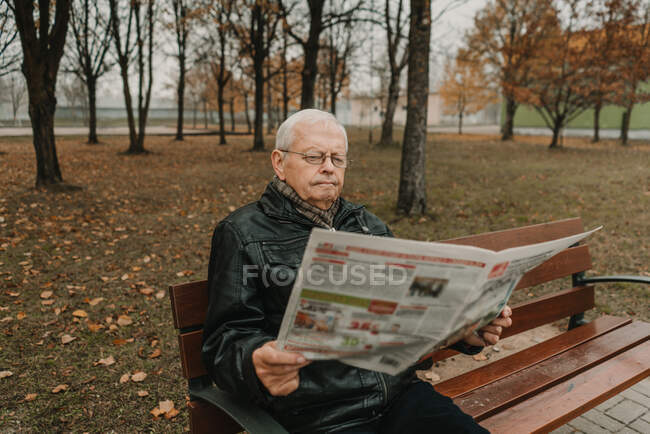 Senior male in leather jacket reading fresh newspaper while sitting on bench in autumn park — Stock Photo