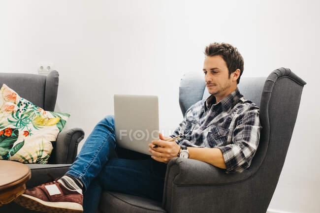 Хлопець у повсякденному одязі з годинником, який працює з ноутбуком і сидить у кріслі біля білої стіни. — стокове фото