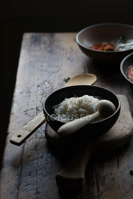 Bowl of rice and empty plate on rustic wooden table on dark background — Stock Photo