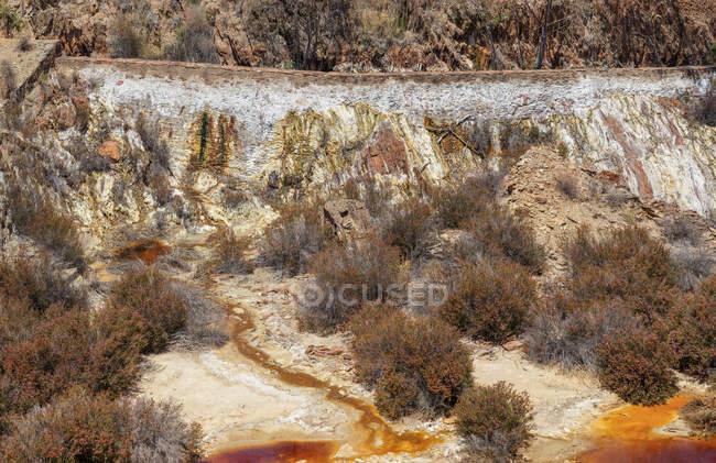 Малые потоки грязной воды, протекающей на склоне ямы в Санто Домингуш шахты в Португалии — стоковое фото