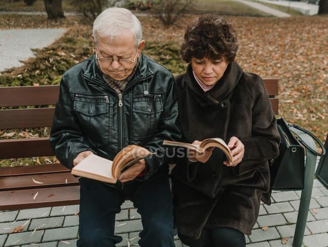 Старшая пара читает книги в парке — стоковое фото