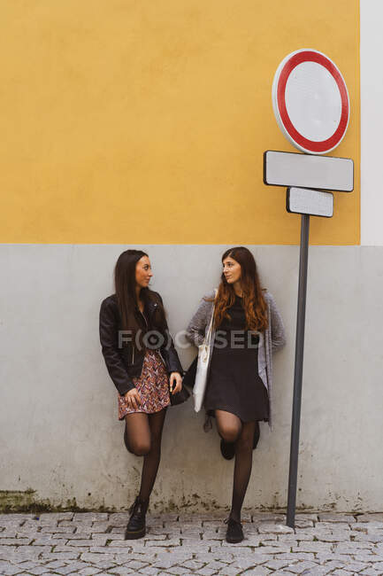 Attractive trendy ladies with legs on grey and brown wall talking on street near road sign in Porto, Portugal — Stock Photo