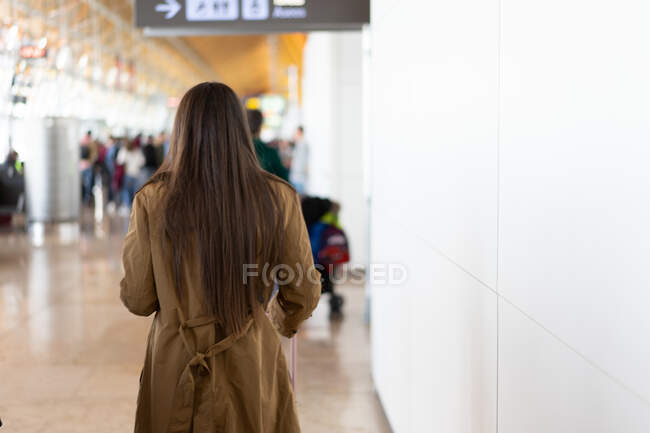 Back view long haired lady in coat going near white wall and people in Porto, Portugal — Stock Photo