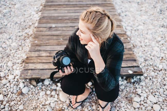 Dall'alto ripresa di una bella donna con macchina fotografica che sorride e distoglie lo sguardo mentre si siede sulla costa rocciosa di Altea, Spagna — Foto stock