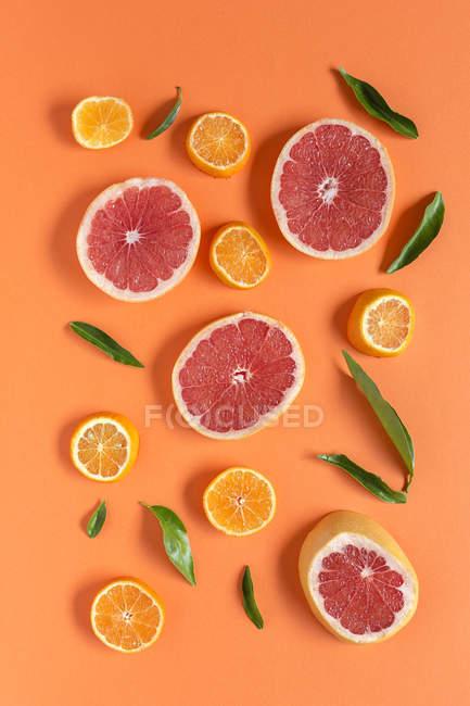 Мандарин и грейпфрутовый ломтик с зелеными листьями на оранжевом фоне — стоковое фото